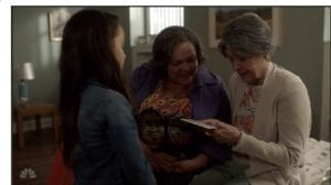 Image of Pilar, Elvia, and young Pilar looking at a family album.