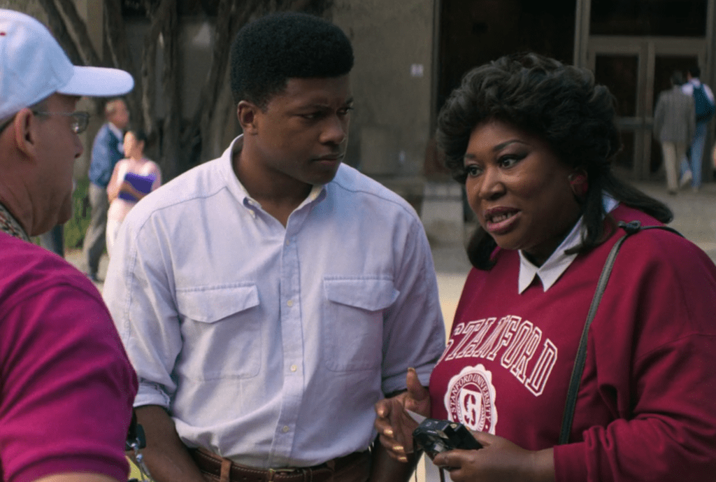 Tamme Dawson on the Stanford campus with her son Ernest, talking to a fan of the show who recognizes Tamme's character. Ernest looks worriedly at Tamme.