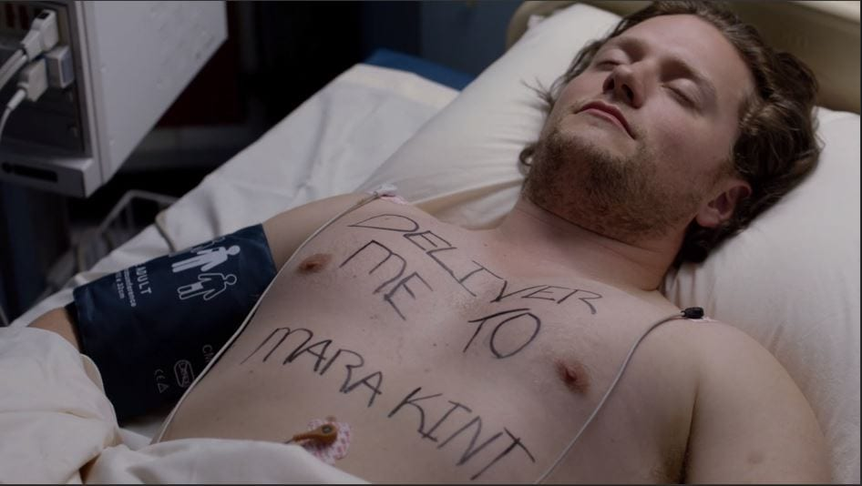 "A man in a bed with ""Deliver me to Mara Kint"" written across his chest"