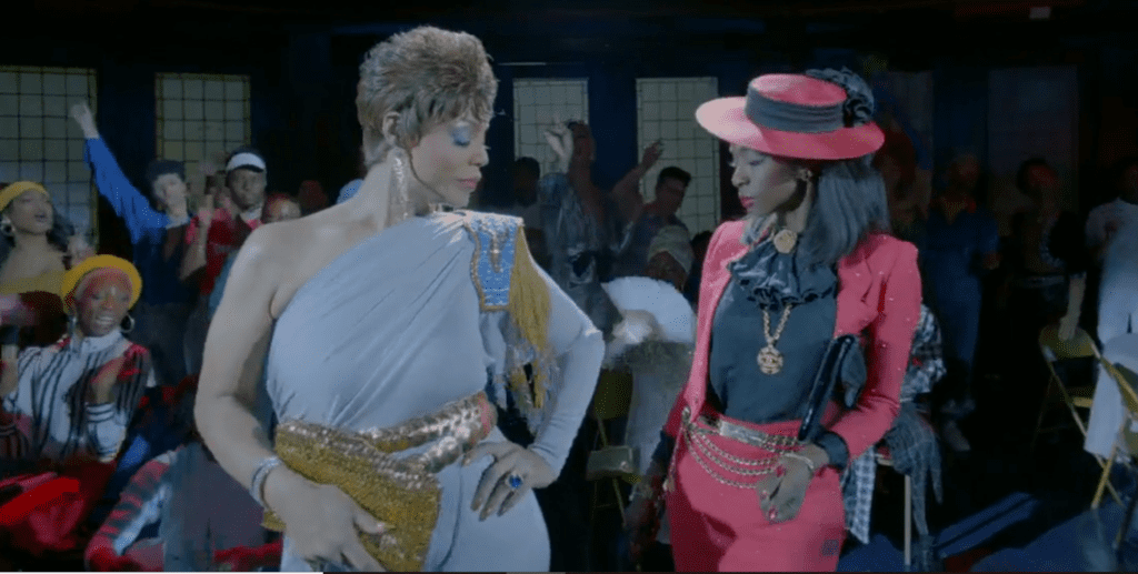 Two gorgeously dressed transgender women stand side by side. One wears a silky light blue jumpsuit with a metallic belt and purse. The other wears a bright pink pantsuit with black blouse and gold jewelry.