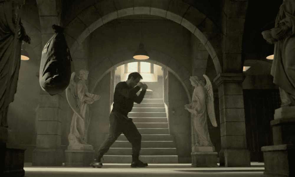 Matt practices boxing in the church basement, under an arched ceiling, flanked by two angel statues.