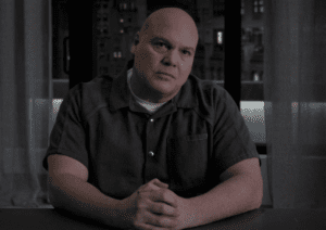 Wilson Fisk sits facing the camera with a calculating expression.