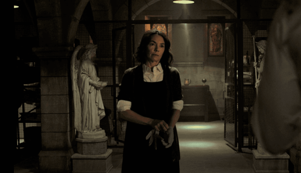 Sister Maggie stands in a church basement. She is wearing white shirtsleeves and a black dress, putting on blue gloves, looking exasperated. Angel statues and stained glass windows are in the background.