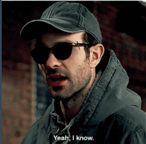 """Closeup of Matt wearing dark glasses, and a cap and hoodie in drab gray. Caption: """"Yeah, I know."""""""