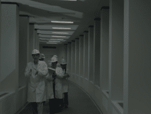 A group of scientists in lab coats and hard hats discuss parallel universes at the Washington Township Facility