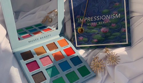 colorful makeup palette and earrings on a white backdrop