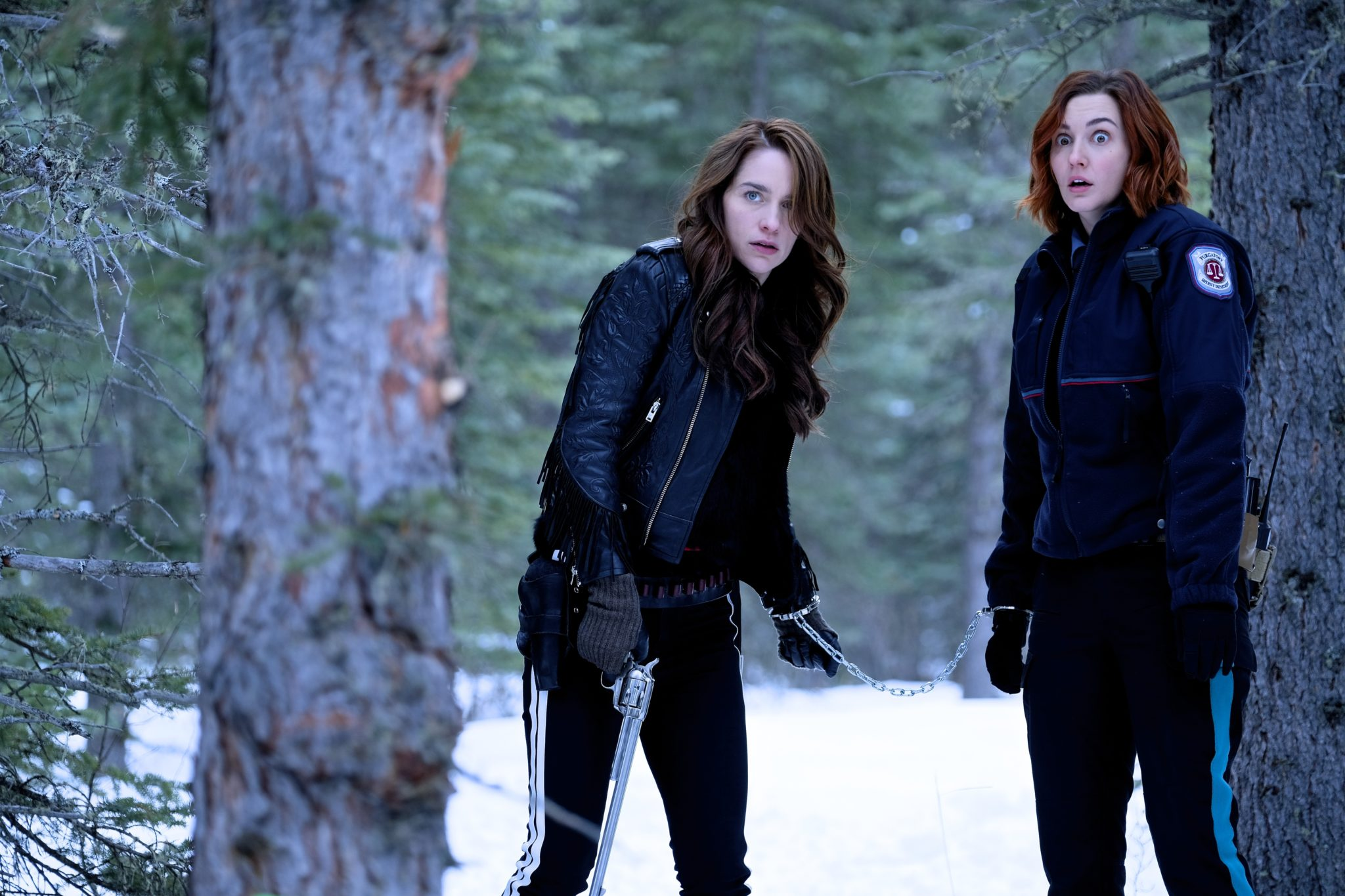 Wynonna and Nicole handcuffed together in the woods.