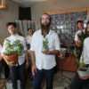 Members of the band Kuwaisiana holding plants.