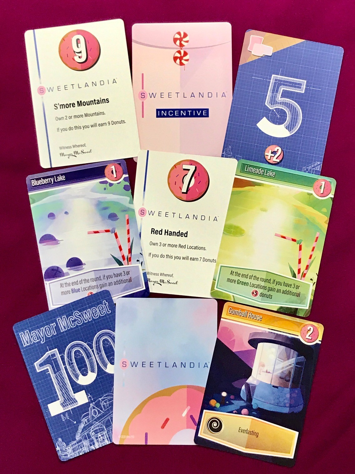 random assortment of cards from sweetlandia showing different locations, incentives, and bidding cards
